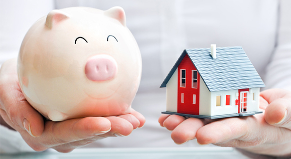 Person holding piggy bank and model house on each hand.