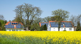 Houses in a field with solar collectors on their roofs.