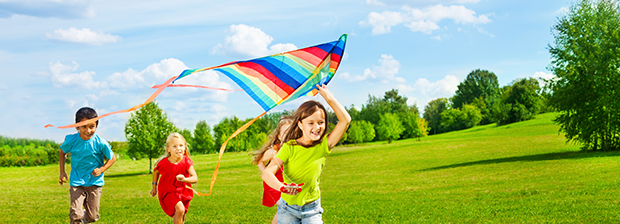 Kids running across a meadow playing with a kite.