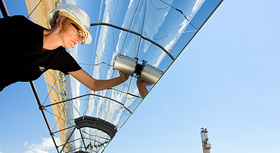 Female engineer inspecting solar panel.