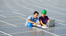 Male and female engineer inspecting PV modules.