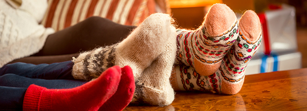 Legs of three people wearing woollen socks on a coffee table.