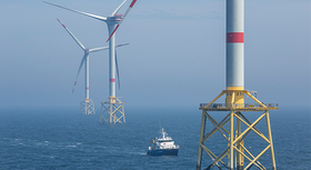 Three off-shore wind turbines and a boat at sea.