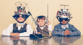 Three kids wearing handcrafted robot gear.