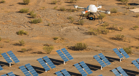 Aerial drone hovering above solar panels in a desert environment.