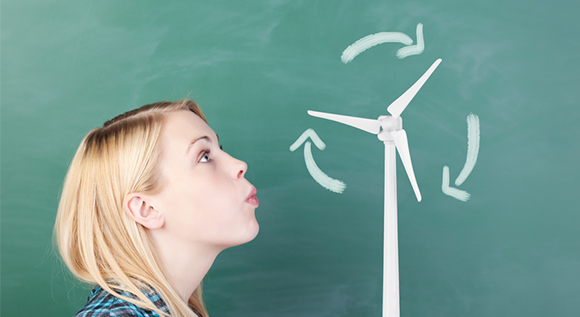 Young woman blowing on an wind turbine