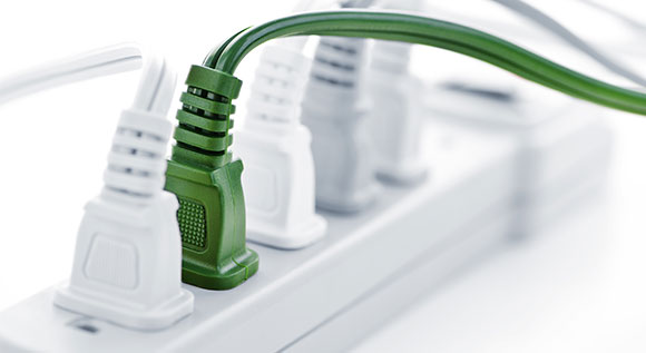 Multiple socket with several white plugs and a green one