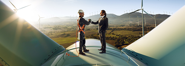 Two men shaking hands on top of a wind generator