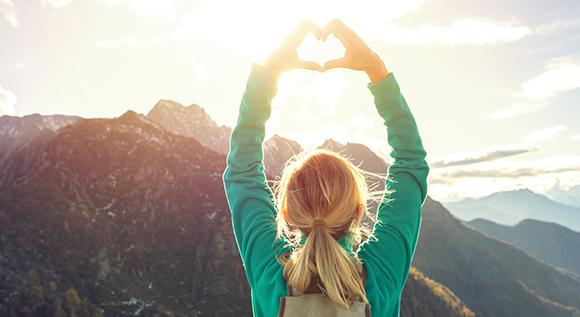 Frau formt mit beiden Händen ein Herz in Gebirgslandschaft.