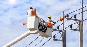 Zwei Arbeiter führen Reparaturarbeiten an einer Stromleitung durch.
