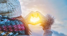 Frau mit Mütze formt Herzsymbl mit ihren Händen in Wintersonne.