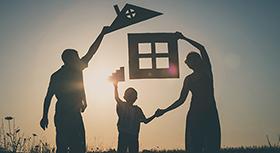Familie hebt Haus aus Pappe in den Händen.