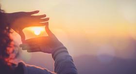 Zwei Hände umrahmen die Sonne